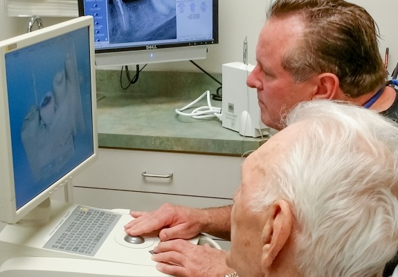 Dotor Schumacher and dental patient looking at digital bite impressions on computer screen