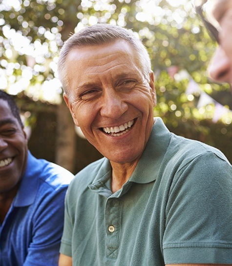 Older man smiling with his friends outdoors