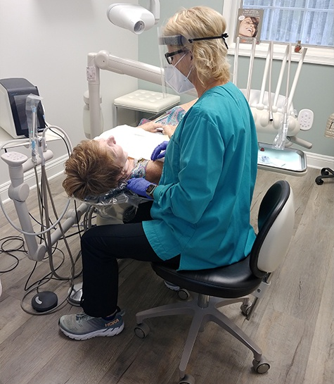 Dental team member providing preventive dentistry treatment for patient