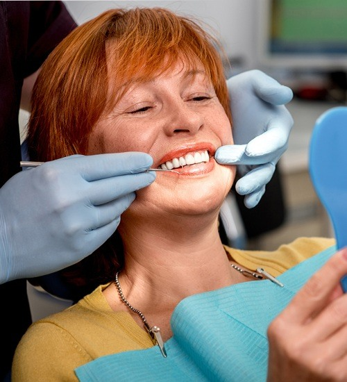 Woman looking at smile during dental checkup and teeth cleaning visit