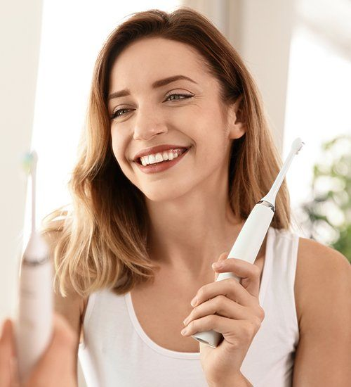 Smiling woman holding electric toothbrush