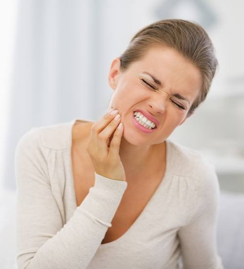 Woman in need of root canal therapy holding cheek in pain