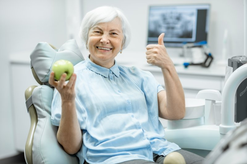 an older woman holding an apple and giving a thumbs up after receiving her new dental implants