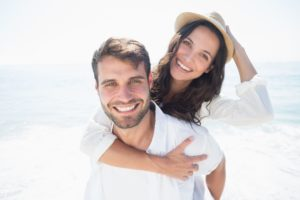 happy couple on the beach showing off their dental implants in Jacksonville